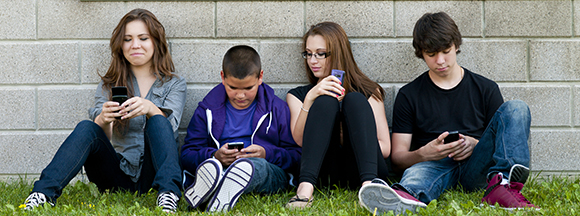 group of teenagers sitting outdoors and using cellphone